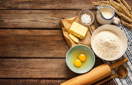 kitchen utensils: Hornear el pastel en la cocina rural - ingredientes de la receta de masa (huevos, harina, leche, mantequilla, az�car) y contacto de balanceo en la mesa de madera de �poca desde arriba. Foto de archivo