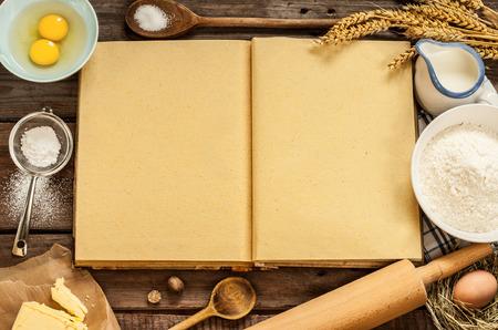 Landelijk vintage houten keukentafel met lege kookboek, bakken cake ingrediënten (eieren, bloem, melk, boter, suiker) en kookgerei rond. Stockfoto