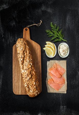 salmon ahumado: Receta Sandwich - bollo de pan, salmón ahumado, queso cottage y eneldo. Ingredientes en el pizarrón negro desde arriba. Foto de archivo