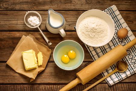 Bakkencake in landelijke keuken - Recept ingrediënten van deeg (eieren, bloem, melk, boter, suiker) en rolletje op vintage houten tafel van boven