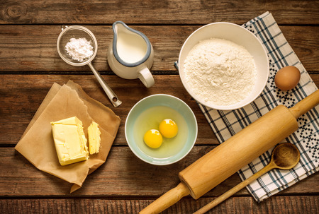 Baking cake in rural kitchen - dough recipe ingredients (eggs, flour, milk, butter, sugar) and rolling pin on vintage wood table from above