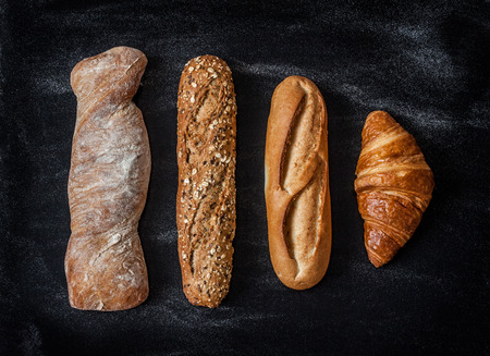 kitchen poster: Different kinds of bread rolls on black chalkboard from above. Kitchen or bakery poster design. Stock Photo