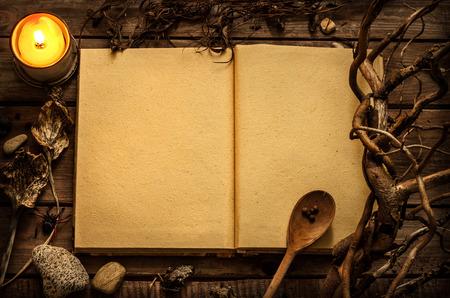 Antigo livro aberto de bruxaria em branco ou receitas mágicas com ingredientes de vela e alquimia ao redor. Fundo rústico misterioso escuro com espaço de texto.