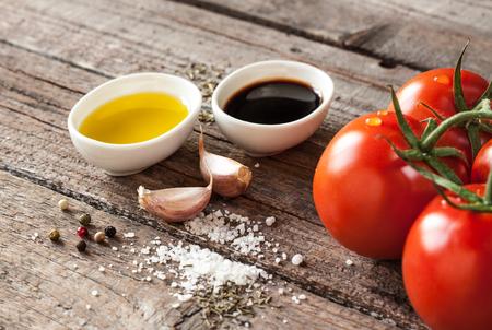 Vinaigrette or french dressing recipe ingredients on vintage wood background. Olive oil, balsamic vinegar, garlic, salt and pepper.