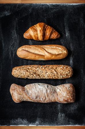 pan frances: Diferentes tipos de pan en la pizarra negro desde arriba. Cocina o el diseño del cartel de la panadería. Foto de archivo