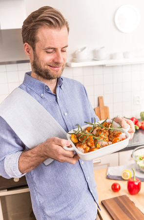 prepared dish: Happy smiling forty years old caucasian man or chef holding roasting dish with raw chicken drumsticks, potatoes and rosemary prepared to bake. Stock Photo