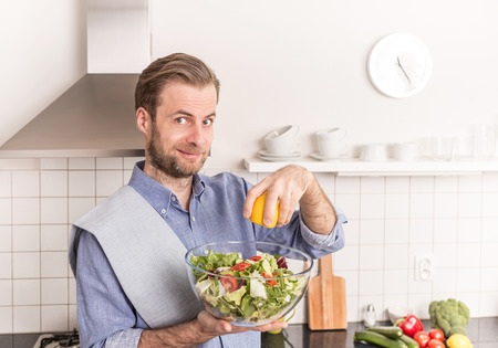 food dressing: Happy smiling forty years old caucasian man making fresh vegetable salad in the kitchen (squeezing lemon juice for dressing). Healthy food and diet concept.