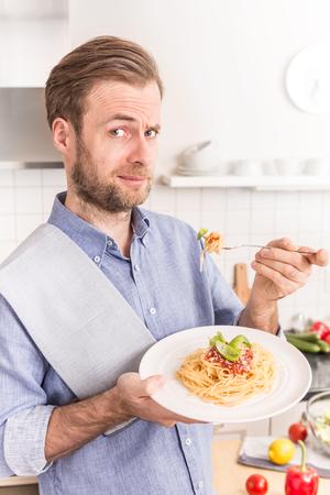 plato del buen comer: Sonrisa feliz de los cuarenta años de edad de raza caucásica hombre o cocinero comer espaguetis a la boloñesa en la cocina - comida italiana.