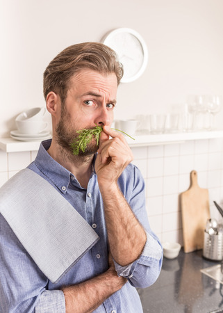 joking: Forty years old caucasian man standing in the kitchen and holding dill next to his nose as mustache. Chef having fun during cooking.