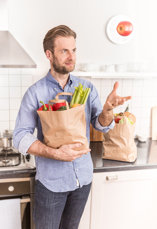 forty: Happy smiling forty years old caucasian man holding paper grocery shopping bag in the kitchen. Stock Photo