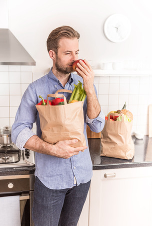 forty: Forty years old caucasian man holding paper grocery shopping bag in the kitchen. Stock Photo