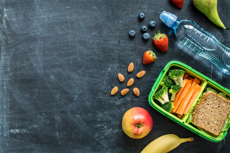 food box: School lunch box with sandwich, vegetables, water, almonds and fruits on black chalkboard. Healthy eating habits concept - background layout with free text space. Flat lay composition (top view).