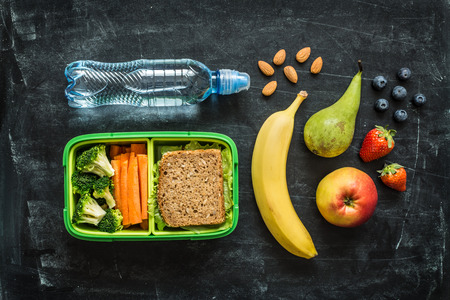eating habits: School lunch box with sandwich, vegetables, water, almonds and fruits on black chalkboard background. Healthy eating habits concept. Flat lay composition (from above, top view). Stock Photo