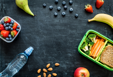 eating habits: School lunch box with sandwich, vegetables, water, almonds and fruits on black chalkboard. Healthy eating habits concept - background layout with free text space. Flat lay composition (top view).