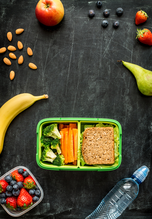 lunch: School lunch box with sandwich, vegetables, water, almonds and fruits on black chalkboard. Healthy eating habits concept - background layout with free text space. Flat lay composition (top view).