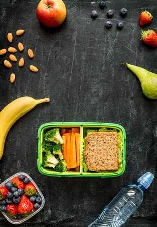 Schule Lunch-Box mit Sandwich, Gemüse, Wasser, Mandeln und Früchte auf schwarz Tafel. Gesunde Ernährung Konzept - Hintergrund-Layout mit Raum für freien Text. Flache Laien Zusammensetzung (Draufsicht).