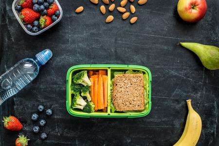 Hábitos saludables: caja de almuerzo escolar con sándwich, vegetales, agua, almendras y frutas en la pizarra negro. Los hábitos alimenticios saludables concepto - diseño de fondo con el espacio de texto libre. composición aplanada (vista desde arriba).