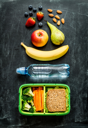 School lunch box with sandwich, vegetables, water, almonds and fruits on black chalkboard background. Healthy eating habits concept. Flat lay composition (from above, top view). Archivio Fotografico