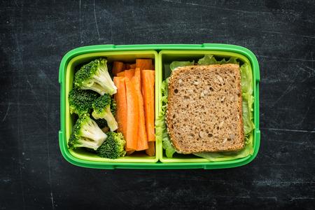 almuerzo: caja de almuerzo de la escuela verde con bocadillo, el brócoli y la zanahoria de cerca sobre fondo negro pizarra. Concepto sano de los hábitos alimenticios. composición aplanada (desde arriba, vista desde arriba).