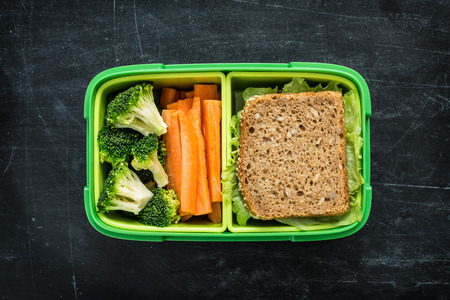 eating habits: Green school lunch box with sandwich, broccoli and carrot close up on black chalkboard background. Healthy eating habits concept. Flat lay composition (from above, top view).