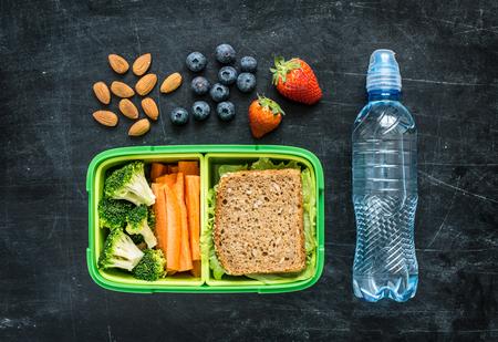 Schule Lunch-Box mit Sandwich, Gemüse, Wasser, Mandeln und Früchte auf schwarzem Tafel Hintergrund. Gesunde Ernährung Konzept. Flache Laien Zusammensetzung (von oben, von oben gesehen).