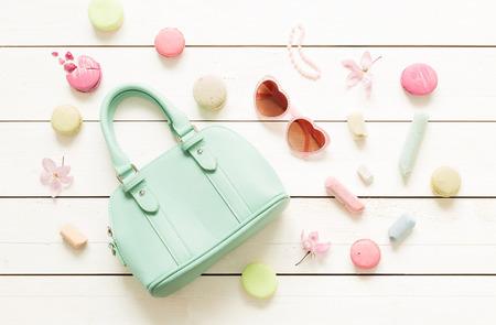 女の子のためのファッション小物 (バッグ、サングラス) したパステル テーマ気分ボードです。白い素朴な木製の背景。(上記、平面図) フラット レ