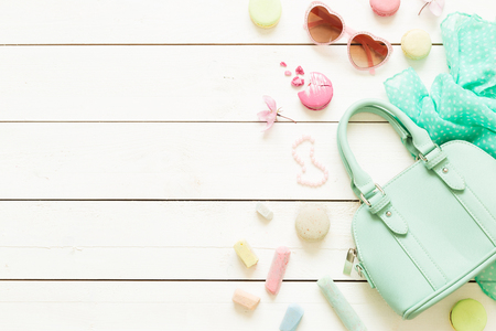 Pastel theme mood board with fashion accessories (bag, sunglasses, scarf) for girls. White rustic wooden background. Flat lay composition (from above, top view). Free text space.
