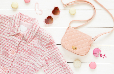 Pastel theme mood board with pink jacket and fashion accessories (bag, sunglasses) for girls. White rustic wooden background. Flat lay composition (from above, top view).