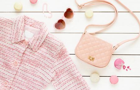 Pastellthema Moodboard mit rosa Jacke und Modeaccessoires (Tasche, Sonnenbrille) für Mädchen. Weißer rustikaler hölzerner Hintergrund. Flache Laienkomposition (von oben, Draufsicht). Lizenzfreie Bilder