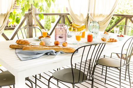 garden scenery: Summer outdoor continental breakfast on the garden terrace. Countryside weekend or rural holiday scenery.