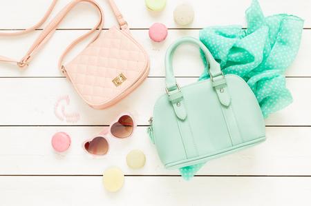 Pastell Thema Moodboard mit Mode-Accessoires (Taschen, Sonnenbrillen, Schal) für Mädchen. Weiß rustikalen hölzernen Hintergrund. Flache Laien Zusammensetzung (von oben, von oben gesehen). Lizenzfreie Bilder