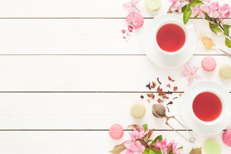 Roze fruitige thee en pastel Franse macarons cakes op rustieke witte houten achtergrond. Dessert in een tuin. Flat lay samenstelling (van boven, bovenaanzicht). Vrije tekst ruimte.