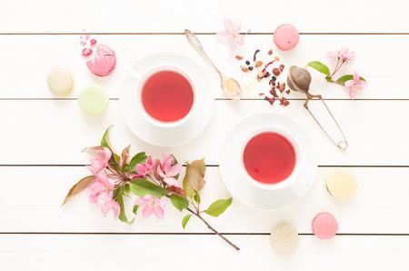 Roze fruitige thee en pastel Franse macarons cakes op rustieke witte houten achtergrond. Dessert in een tuin. Flat lay samenstelling (van boven, bovenaanzicht). Stockfoto