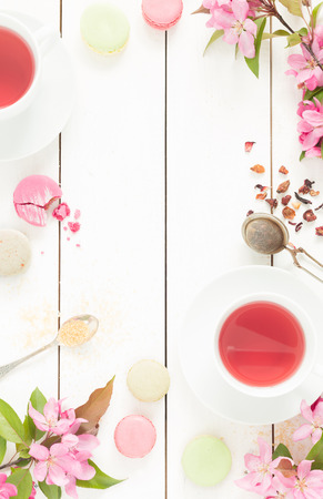 Pink fruity tea and pastel french macarons cakes on rustic white wooden background. Dessert in a garden. Flat lay composition (from above, top view). Free text space. Archivio Fotografico