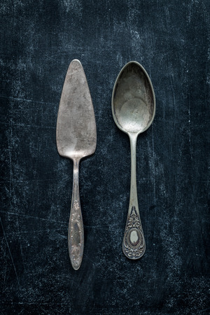 silver cutlery: Old vintage silverware (cutlery) on black chalkboard background from above (top view).
