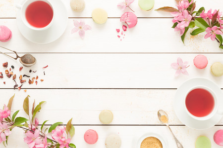 Pink fruity tea and pastel french macarons cakes on rustic white wooden background. Dessert in a garden. Flat lay composition (from above, top view). Free text space. Stock Photo