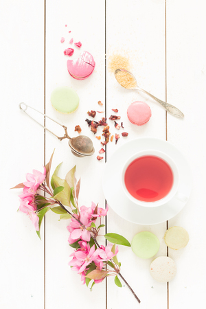 Pink fruity tea and pastel french macarons cakes on rustic white wooden background. Dessert in a garden. Flat lay composition (from above, top view).