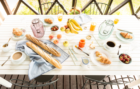garden scenery: Summer outdoor continental breakfast on the garden terrace. Countryside weekend or rural holiday scenery captured from above (top view). Stock Photo