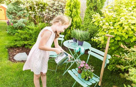 eight years old: Eight years old blond caucasian child girl watering flowers outdoor in a summer garden.