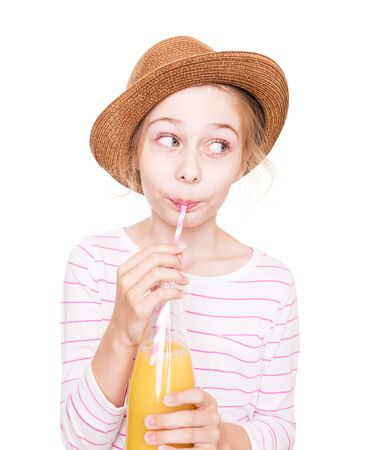 Happy eight years old pretty blond caucasian child girl in a hat with a bottle of fruit juice drink (isolated on white background). Stock Photo