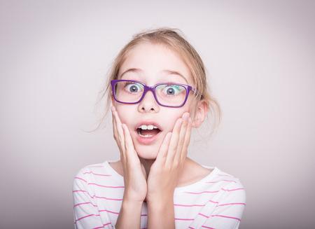 Sorprendido o conmocionado a la cara de ocho años de edad bastante rubia caucásica muchacha del niño en gafas de color violeta. Choque - expresión facial. Diseño con copia espacio libre.