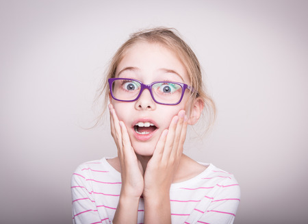 surprised child: Surprised or shocked face of eight years old pretty blond caucasian child girl in violet glasses. Shock - facial expression. Layout with free copy space.