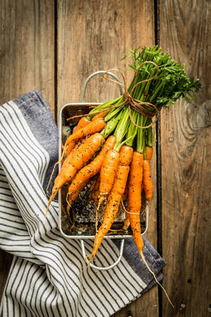 marchew: Bunch of young or baby carrots on vintage rustic wooden table from above (top view). Fresh harvest from the garden in the rural kitchen. Background layout with free text space.