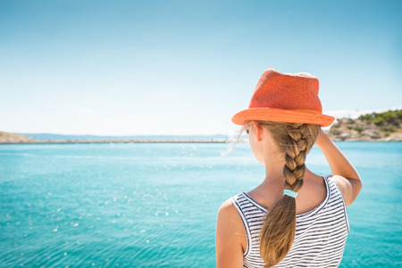 summer holidays: Blond child girl in orange hat standing back on the beach during sunny day. Blue sea as background. Childhood - summer vacation (holiday), travelling. Stock Photo