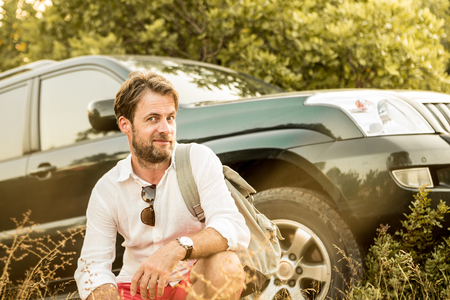 Forty years old caucasian man in front of his four-wheel drive SUV car. Driver having a break outdoor during safari adventure trip. Stock Photo