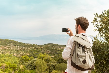 takes: Tourist man takes a photo of beautiful landscape with mobile phone (smartphone). Hills and sea as background. Summer vacation (holiday), traveling and adventure.