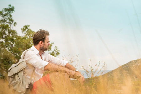 adventure holiday: Forty years old caucasian tourist man taking a break while mountain trip. Meadow and hills as background. Summer vacation (holiday), traveling and adventure. Stock Photo