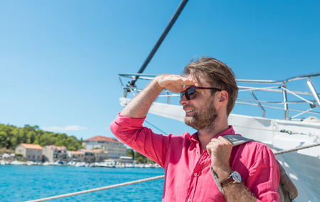 adventure holiday: Forty years old caucasian tourist man or sailor in sunglasses standing by the sea marina with backpack. Yacht boat as background. Summer vacation (holiday), traveling and adventure.