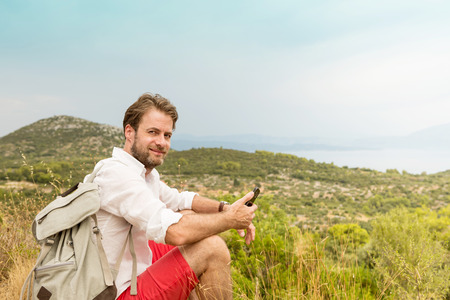 adventure holiday: Happy smiling forty years old caucasian tourist man taking a break while mountain trip. Hills and sea as background. Summer vacation (holiday), traveling and adventure. Stock Photo