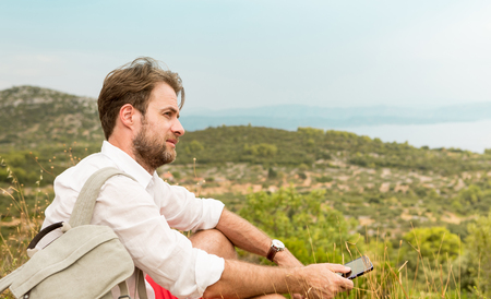 adventure holiday: Forty years old caucasian tourist man taking a break while mountain trip. Hills and sea as background. Summer vacation (holiday), traveling and adventure. Stock Photo